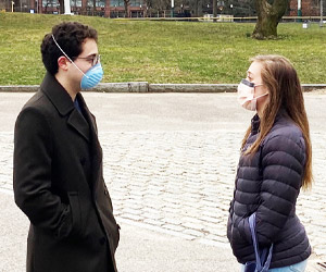 Daniel Schlessinger with his girlfriend Steffi, both wearing masks, in a Boston Park
